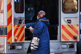 NEW YORK, NY - APRIL 11: A relative stands near to a patient being taken away in an ambulance on April 11, 2020 in the Brooklyn borough of New York City. According to John Hopkins University, the global death toll from COVID-19 has now reached 100,000 worldwide with many experts believing that the number is actually higher.   Spencer Platt/Getty Images/AFP == FOR NEWSPAPERS, INTERNET, TELCOS & TELEVISION USE ONLY ==