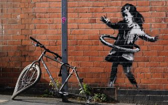 File photo dated 15/10/20 of graffiti artwork, which has been confirmed as the work of street artist Banksy. The artwork, on a side of a property at Rothesay Avenue and Ilkeston Road, Nottingham, depicts a young girl playing with a tyre and is painted on a wall near to an abandoned bicycle that is missing a wheel. (Nottingham - 2020-10-17, Tim Goode / IPA) p.s. la foto e' utilizzabile nel rispetto del contesto in cui e' stata scattata, e senza intento diffamatorio del decoro delle persone rappresentate