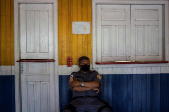 epa08822808 A military policeman guards the only electoral center of the Lago do Catalao community, in the rural area of Iranduba, Amazonas, Brazil, 15 November 2020. Brazilians go to the polls this Sunday to renew the mayors and councilors of 5,569 cities in the country, in a process that passed almost without incidents and under strict security measures due to covid-19. In Lago do Catalao, where all the houses are on the water, voters go by boat to cast their vote at the community school.  EPA/RAPHAEL ALVES
