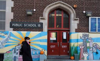 epa08828423 A person walks past a public school in Brooklyn, New York, USA, 18 November 2020. New York City Mayor Bill de Blasio announced on 18 November that the city s entire public school system, the largest in the country, will indefinitely suspend all in-school classes as a result of the rising COVID-19 positivity rate from 19 november 2020..  EPA/JUSTIN LANE