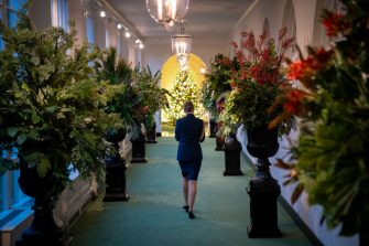 """WASHINGTON, DC - NOVEMBER 30: A military aide walks through the East Colonnade as it is decorated for Christmas at the White House on November 30, 2020 in Washington, DC. This year's theme for the White House Christmas decorations is """"America the Beautiful."""" (Photo by Drew Angerer/Getty Images)"""