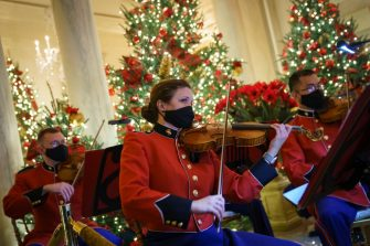 """WASHINGTON, DC - NOVEMBER 30: A military band plays Christmas music in the Grand Foyer of the White House on November 30, 2020 in Washington, DC. This year's theme for the White House Christmas decorations is """"America the Beautiful."""" (Photo by Drew Angerer/Getty Images)"""