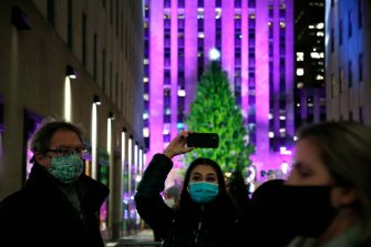 NEW YORK, NEW YORK - DECEMBER 02: People take photos of the Christmas tree during the 87th Annual Rockefeller Center Christmas Tree Lighting Ceremony at Rockefeller Center on December 02, 2020 in New York City. (Photo by John Lamparski/Getty Images)