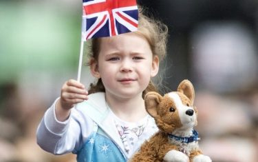 CHESTER, ENGLAND - JUNE 14:  A young girl holds a flag and toy Corgi as well wishers line the route as the Duchess of Sussex and Queen Elizabeth II walk from Storyhouse to Chester Town Hall on June 14, 2018 in Chester, England. Meghan Markle married Prince Harry last month to become The Duchess of Sussex.  This is her first engagement with the Queen. During the visit the pair opened a road bridge in Widnes, visited The Storyhouse in Chester followed by the Town Hall.  (Photo by Anthony Devlin/Getty Images)