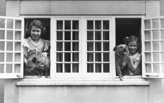 The Royal Princesses Elizabeth and Margaret (1930 - 2002) at the windows of the Royal Welsh House with two Corgi dogs, June 1936.  (Photo by Lisa Sheridan/Studio Lisa/Hulton Archive/Getty Images)