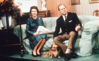 BALMORAL, SCOTLAND - 1974:  HM Queen Elizabeth II and Prince Philip, Duke of Edinburgh relax with their corgis and a newspaper at Balmoral Castle in 1974 in Balmoral, Scotland. (Photo by Anwar Hussein/Getty Images)