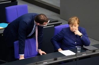epa08870052 German Minister of Health Jens Spahn (L) and German Chancellor Angela Merkel (R) during a session of the German parliament 'Bundestag' in Berlin, Germany, 08 December 2020. Members of Bundestag debated on the Budget Act 2021.  EPA/HAYOUNG JEON