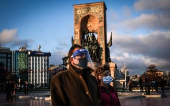 epa08866574 Tourists wearing face mask walk in front of the Republic Monument at the Taksim Square during weekend lockdown in Istanbul, Turkey, 06 December 2020. Turkey imposed curfews on weekdays after 9pm and full weekend lockdowns with the exception of tourists to combat the spread of coronavirus, after a recent spike in Covid-19 infections and related deaths.  EPA/SEDAT SUNA