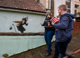 epa08875127 Locals gather to see the new creation entitled 'Aachoo!!' by British street artist Banksy that appeared on Vale Street overnight in Bristol, Britain, 10 December 2020. The painting depicts an old woman sneezing with her false teeth flying out.  EPA/JON ROWLEY