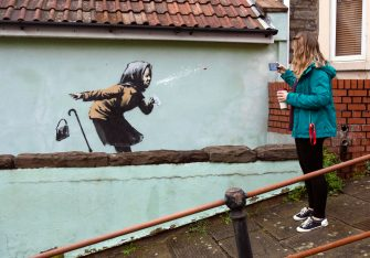 epa08875138 Locals gather to see the new creation entitled 'Aachoo!!' by British street artist Banksy that appeared on Vale Street overnight in Bristol, Britain, 10 December 2020. The painting depicts an old woman sneezing with her false teeth flying out.  EPA/JON ROWLEY