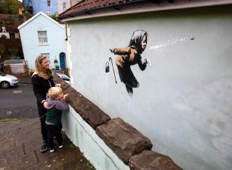 epa08875135 Locals gather to see the new creation entitled 'Aachoo!!' by British street artist Banksy that appeared on Vale Street overnight in Bristol, Britain, 10 December 2020. The painting depicts an old woman sneezing with her false teeth flying out.  EPA/JON ROWLEY