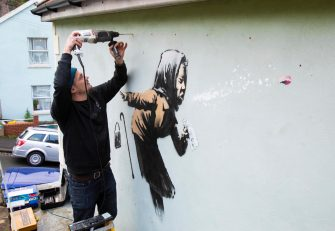 epa08875161 Fred Loosmore places a protective perspex covering over the new creation entitled 'Aachoo!!' by British street artist Banksy that appeared on Vale Street overnight in Bristol, Britain, 10 December 2020. The painting depicts an old woman sneezing with her false teeth flying out.  EPA/JON ROWLEY