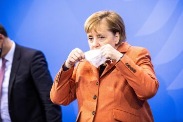 epaselect epa08881126 German Chancellor Angela Merkel puts her face mask on during a press conference after a video conference with German State Premiers about increased anti-coronavirus measures to be implemented on upcoming 16 December, in Berlin, Germany, 13 December 2020.  EPA/RAINER KEUENHOF / POOL
