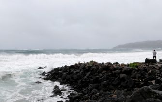 BYRON BAY, AUSTRALIA - DECEMBER 14:  A man watches the severe swell which resulted in along stretch of beach erosion due to heavy rain on December 14, 2020 in Byron Bay, Australia. Byron Bay's beaches face further erosion as wild weather and hazardous swells lash the northern NSW coastlines. (Photo by Regi Varghese/Getty Images)