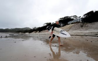 BYRON BAY, AUSTRALIA - DECEMBER 14:  A surfer seen waling along the stretch of coastal areas seen disappeared due to erosion along the beach side, December 14, 2020 in Byron Bay, Australia. Byron Bay's beaches face further erosion as wild weather and hazardous swells lash the northern NSW coastlines. (Photo by Regi Varghese/Getty Images)