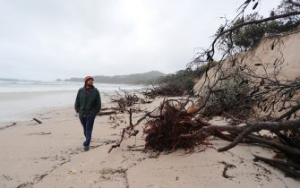 BYRON BAY, AUSTRALIA - DECEMBER 14:  Local resident Nick Colby checks the damage due to erosion along the beach side, December 14, 2020 in Byron Bay, Australia. Byron Bay's beaches face further erosion as wild weather and hazardous swells lash the northern NSW coastlines. (Photo by Regi Varghese/Getty Images)