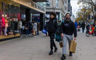epa08856930 Shoppers walk past queues outside Debenhams in Oxford Street, London, Britain, 02 December 2020. The second Coronavirus UK national lockdown ended on 02 December, allowing non-essential shops to trade ahead of the traditionally busy Christmas season.  EPA/VICKIE FLORES