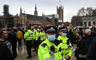 epa08883654 Police try to stop people from gathering outside parliament during an anti-lockdown protest in London, Britain, 14 December 2020. According to news reports London is facing a move to tier 3 after rise in Coronavirus cases in capital. This will mean the closure of retail stores, pubs and restaurants, causing further pain to the UK economy.  EPA/ANDY RAIN