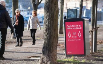 epa08831209 People strollIing in the cold but sunny weather pass a sign asking to maintain social distancing, amid the continuous spread of the coronavirus disease (COVID-19) pandemic, in Stockholm, Sweden, 20 November 2020.  EPA/Fredrik Sandberg SWEDEN OUT