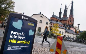 epa08761812 A woman passes a trash can with a sign reading 'The danger is not over - Keep your distance' in a pedestrian street in central Uppsala, Sweden, 21 October 2020. Due to an increase of Covid-19 cases in the region of Uppsala, new local recommended restrictions has been instated to curb the corona pandemic.  EPA/Claudio Bresciani SWEDEN OUT