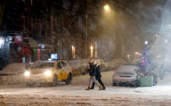 epa08889116 People cross the road in the East Village of New York, USA, 16 December 2020. New York City restaurants have been ordered to close outdoor dining areas as forecasts expect up to 35 centimeters of snow.  EPA/JASON SZENES
