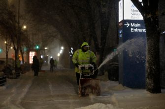 epa08889136 A worker clears snow from a footpath in New York, USA, 16 December 2020. According to forecasts, New York City is to expect up to 35 centimeters of snow.  EPA/Peter Foley