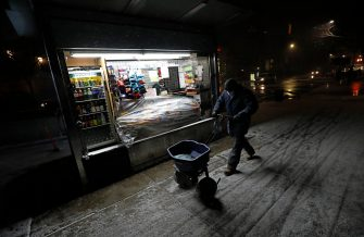 epa08889090 A worker spreads salt on Ninth Avenue as snow falls in New York, New York, USA, 16 December 2020. Forecasters are predicting up to 14 inches of snow with strong winds that could create blizzard-like conditions. A winter weather advisory is in effect.  EPA/PETER FOLEY