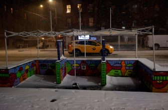epa08889113 A New York City Taxi drives past an empty outside dining area in the East Village of New York, USA, 16 December 2020. New York City restaurants have been ordered to close outdoor dining areas as forecasts expect up to 35 centimeters of snow.  EPA/JASON SZENES