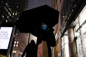 epa08889089 A woman carries an umbrella up Eighth Avenue as snow falls in New York, New York, USA, 16 December 2020. Forecasters are predicting up to 14 inches of snow with strong winds that could create blizzard-like conditions. A winter weather advisory is in effect.  EPA/PETER FOLEY