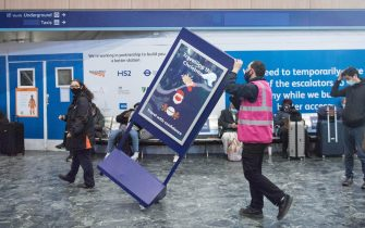 A station employee removes a 'Travelling at Christmas' sign from Euston station, London, with the public being urged to adhere to Government guidance after Prime Minister Boris Johnson announced on Saturday that from Sunday areas in the South East currently in Tier 3 will be moved into a new Tier 4 for two weeks Ð effectively returning to the lockdown rules of November, after scientists warned of the rapid spread of the new variant coronavirus. (London - 2020-12-20, Stefan Rousseau / IPA) p.s. la foto e' utilizzabile nel rispetto del contesto in cui e' stata scattata, e senza intento diffamatorio del decoro delle persone rappresentate