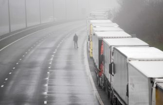 epa08897811 A driver waits by lorries headed to the Port of Dover which are stacked along the M20 motorway in Kent, Britain, 21 December 2020. France has closed its border with the UK for 48 hours over concerns about the new coronavirus variant. Freight lorries cannot cross by sea or through the Eurotunnel and the Port of Dover has closed to outbound traffic.  EPA/NEIL HALL