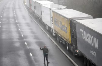 epa08897812 A driver waits by lorries headed to the Port of Dover which are stacked along the M20 motorway in Kent, Britain, 21 December 2020. France has closed its border with the UK for 48 hours over concerns about the new coronavirus variant. Freight lorries cannot cross by sea or through the Eurotunnel and the Port of Dover has closed to outbound traffic.  EPA/NEIL HALL