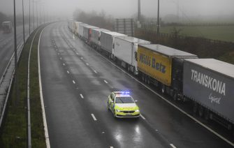 epa08897800 A police car patrols lorries headed to the Port of Dover which are stacked along the M20 motorway in Kent, Britain, 21 December 2020. France has closed its border with the UK for 48 hours over concerns about the new coronavirus variant. Freight lorries cannot cross by sea or through the Eurotunnel and the Port of Dover has closed to outbound traffic.  EPA/NEIL HALL