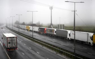 epa08897807 Lorries headed to the Port of Dover are stacked along the M20 motorway in Kent, Britain, 21 December 2020. France has closed its border with the UK for 48 hours over concerns about the new coronavirus variant. Freight lorries cannot cross by sea or through the Eurotunnel and the Port of Dover has closed to outbound traffic.  EPA/NEIL HALL