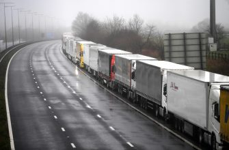 epa08897808 Lorries headed to the Port of Dover are stacked along the M20 motorway in Kent, Britain, 21 December 2020. France has closed its border with the UK for 48 hours over concerns about the new coronavirus variant. Freight lorries cannot cross by sea or through the Eurotunnel and the Port of Dover has closed to outbound traffic.  EPA/NEIL HALL