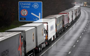 epa08897805 Lorries headed to the Port of Dover are stacked along the M20 motorway in Kent, Britain, 21 December 2020. France has closed its border with the UK for 48 hours over concerns about the new coronavirus variant. Freight lorries cannot cross by sea or through the Eurotunnel and the Port of Dover has closed to outbound traffic.  EPA/NEIL HALL