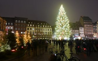 Pedestrians look at the giant Christmas tree on the main square in Strasbourg, eastern France, on November 27, 2020, on the opening day of the city's Christmas Illuminations. - Strasbourg, whose Christmas market is usually one of the most famous, lit up its streets and huge fir tree on November 27, 2020, without the traditional wooden chalets or the crowd of visitors invited to enjoy the show behind their screens. (Photo by FREDERICK FLORIN / AFP) (Photo by FREDERICK FLORIN/AFP via Getty Images)