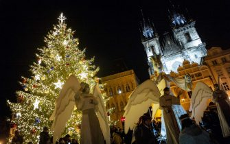 Men wearing angel costumes gesture as people gather around the illuminated Christmas tree at the Old Town Square in Prague on November 29, 2020, amid the ongoing coronavirus Covid-19 pandemic. - The Czech Republic will ease the restrictions aimed at curbing the spread of Covid-19 from December 3, 2020, said on November 29, 2020 the Czech minister of health, Jan Blatny. All restaurants and pubs will be allowed to re-open, with limited indoor seating. Non-essential shops and fitness centers will also re-open as long as there's only one person per 15 square meters. Religious services may resume, and a nighttime curfew will be lifted. (Photo by Michal Cizek / AFP) (Photo by MICHAL CIZEK/AFP via Getty Images)
