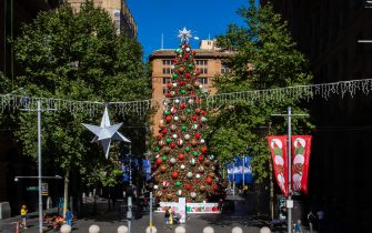 SYDNEY, AUSTRALIA - DECEMBER 23: People walk past a Christmas tree in Martin Place on December 23, 2020 in Sydney, Australia. Sydney's northern beaches are on lockdown, as a cluster of COVID-19 cases continue to grow, causing other Australian states and territories to impose restrictions on travel ahead of the Christmas holidays. As the list of venues impacted across Sydney increases, people are encouraged to get tested and isolate. (Photo by Jenny Evans/Getty Images)
