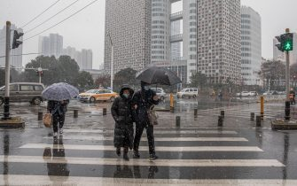 epa08908868 People wearing protective face masks cross a road with an umbrella protecting them from the snow in Wuhan, China, 29 December 2020. Life in Wuhan, a Chinese city of more than 11 million, which nearly a year ago became the epicenter of the coronavirus outbreak is returning to normal. Since May the capital of Hubei province has not recorded locally-transmitted cases of coronavirus disease (COVID-19).  EPA/ROMAN PILIPEY