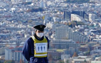 epa08889218 A security guard wearing a face mask stands on an observation deck in Tokyo, Japan, 04 December 2020 (issued 17 December 2020). According to media reports, Tokyo recorded more than 800 infection of SARS-CoV-2 on 17 December, a record daily number.  EPA/FRANCK ROBICHON