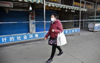 epa08143670 A woman wears a mask while walking past the closed Huanan Seafood Wholesale Market, which has been linked to cases of a new strain of Coronavirus identified as the cause of the pneumonia outbreak in Wuhan, Hubei province, China, 20 January 2020. China reported on 20 January an additional death and surge of 139 new confirmed cases of the mysterious SARS-like virus linked to the Wuhan pneumonia outbreak, bringing the total number of cases to 198 with three deaths so far.  EPA/STR CHINA OUT