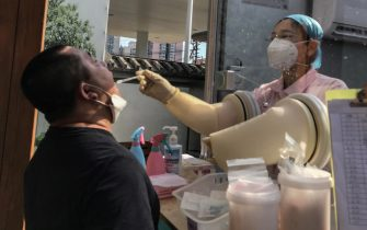 epa08517227 A medical worker performs a COVID-19 test on a man at a hospital in Beijing, China, 30 June 2020. According to media reports, China has reinstated a strict lockdown in Anxin county of Hebei province, near Chinese capital Beijing. The lockdown is expected to effecting about 400,000 people.  EPA/WU HONG