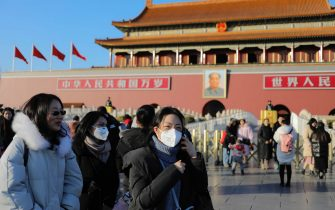 epa08144033 Chinese people wear masks near the Ttiananmen Gate Tower in Beijing, China, 20 January 2020. China reported on 20 January an additional death and surge of 139 new confirmed cases of the mysterious SARS-like virus linked to the Wuhan pneumonia outbreak.  EPA/WU HONG