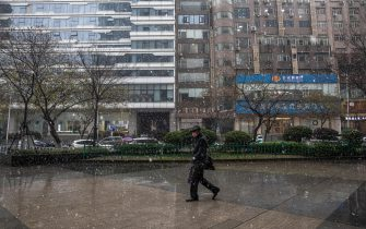 epa08908867 A man wearing a protective face mask walks under the snow in Wuhan, China, 29 December 2020. Life in Wuhan, a Chinese city of more than 11 million, which nearly a year ago became the epicenter of the coronavirus outbreak is returning to normal. Since May the capital of Hubei province has not recorded locally-transmitted cases of coronavirus disease (COVID-19).  EPA/ROMAN PILIPEY