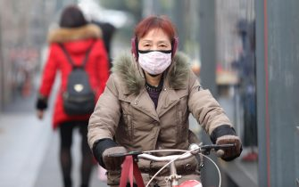 epa08143671 A Chinese cyclist is seen with a mask while riding past a bus station near the closed Huanan Seafood Wholesale Market, which has been linked to cases of a new strain of Coronavirus identified as the cause of the pneumonia outbreak in Wuhan, Hubei province, China, 20 January 2020. China reported on 20 January an additional death and surge of 139 new confirmed cases of the mysterious SARS-like virus linked to the Wuhan pneumonia outbreak, bringing the total number of cases to 198 with three deaths so far.  EPA/STR CHINA OUT