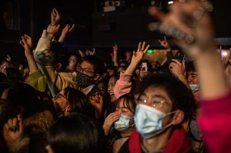 epaselect epa08911726 People with and without protective masks on their faces dance during a concert at a live house in Wuhan, China, 30 December 2020. Life in Wuhan, a Chinese city of more than 11 million, which nearly a year ago became the epicenter of the coronavirus outbreak is returning to normal. Since May the capital of Hubei province has not recorded locally-transmitted cases of Covid-19. Nearly half a million of Wuhan's residents may have been infected with coronavirus, which is almost 10 times its official number of around 50,000 Covid-19 cases in the city, according to a study by the Chinese Center for Disease Control and Prevention.  EPA/ROMAN PILIPEY