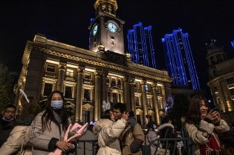 epa08912729 People take selfies as they celebrate the New Year in Wuhan, China, 01 January 2021. Life in Wuhan, a Chinese city of more than 11 million, which nearly a year ago became the epicenter of the coronavirus outbreak is returning to normal.  EPA/ROMAN PILIPEY