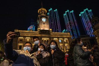 epa08912730 People take selfies as they celebrate the New Year in Wuhan, China, 01 January 2021. Life in Wuhan, a Chinese city of more than 11 million, which nearly a year ago became the epicenter of the coronavirus outbreak is returning to normal.  EPA/ROMAN PILIPEY