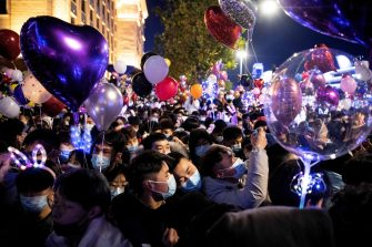 People wearing face masks attend a New Year's countdown in Wuhan in China s central Hubei province on December 31, 2020. (Photo by NOEL CELIS / AFP)